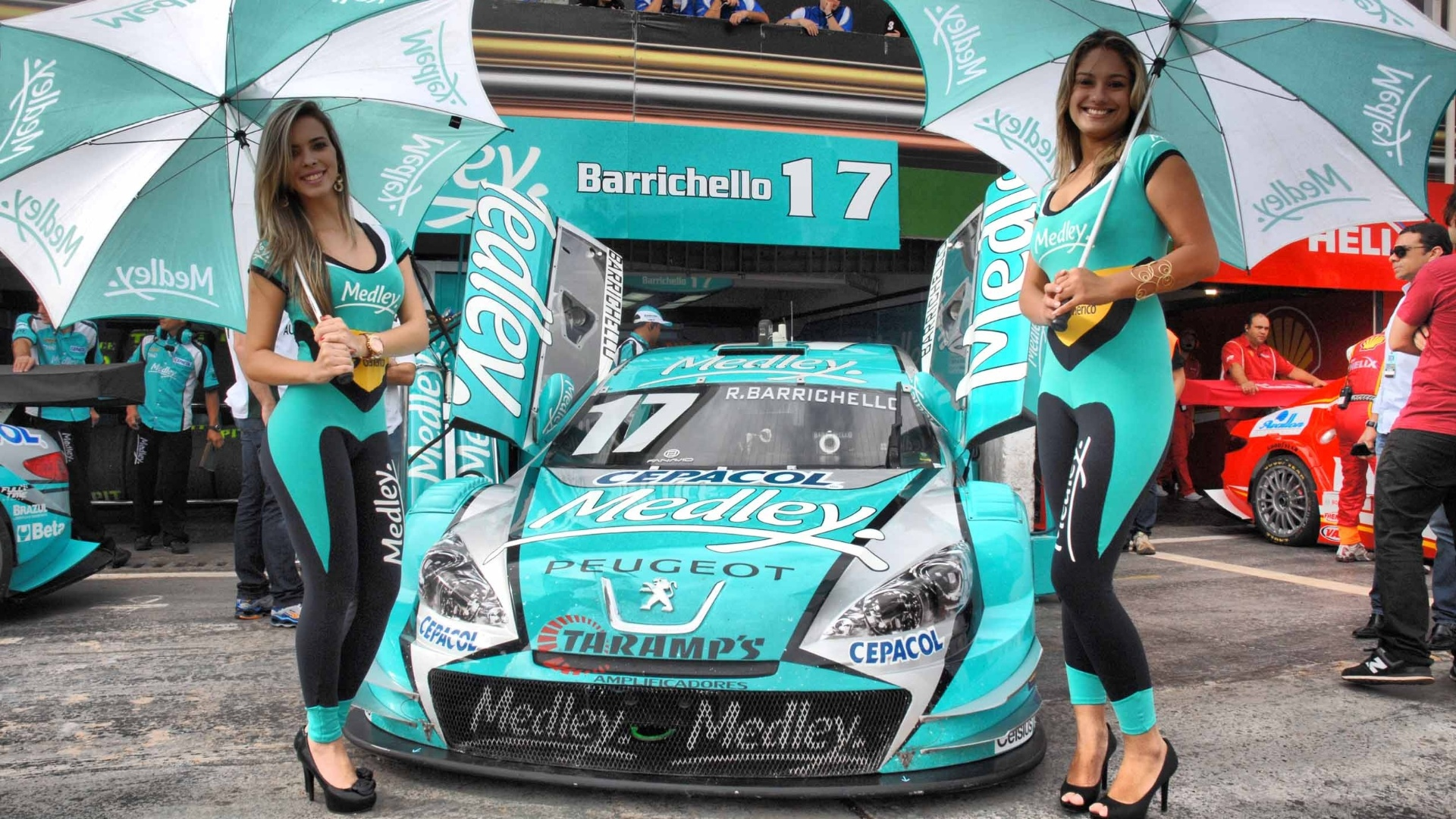 Grid girls da Medley posam com macaco justo  frente dos boxes de Rubens Barrichello