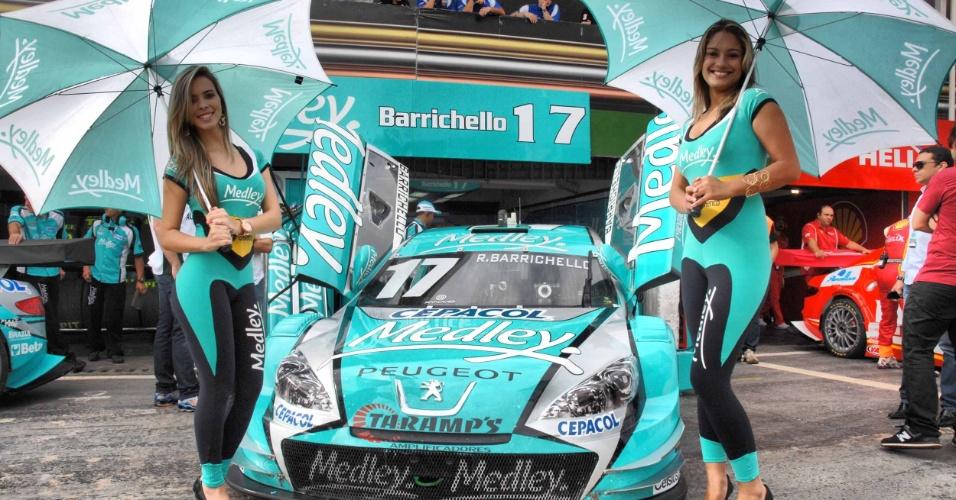 Grid girls da Medley posam com macacão justo à frente dos boxes de Rubens Barrichello