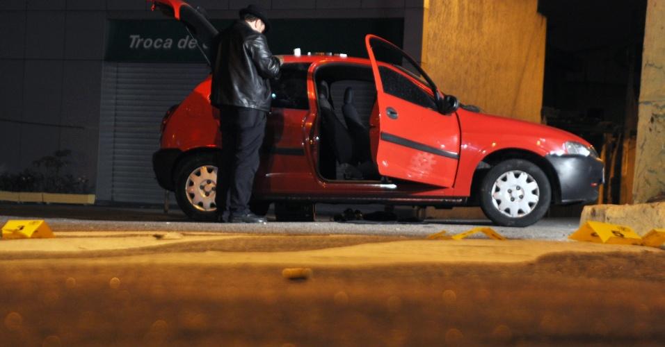 Peritos trabalham no carro de homem que morreu durante troca de tiros com policiais militares
