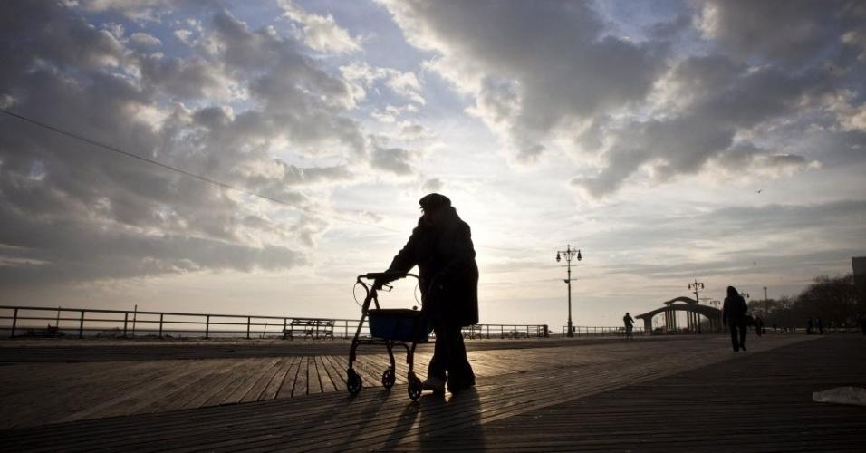 13.nov.2012 - Mulher caminha no calçadão da praia de Brighton, no Brooklyn, em Nova York (EUA), uma das regiões atingidas pela tempestade Sandy que matou pelo menos 121 pessoas no país