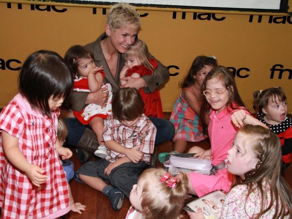 Xuxa Meneghel se reuniu com várias crianças portadoras da Síndrome de Down para lançar o calendário beneficente Happy Down 2013 em uma livraria no Rio de Janeiro (13/11/2012)