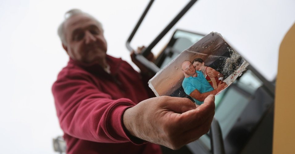 13.nov.2012 - Bill Unger, operador de máquinas pesadas, trabalha nas áreas afetadas pelo furacão Sandy, em  Staten Island, Nova York (EUA). Ele afirma estar entregando à filha as fotos que encontra nos escombros, para que ela coloque essas imagens no Facebook, onde os residentes locais poderão visualizar as imagens futuramente