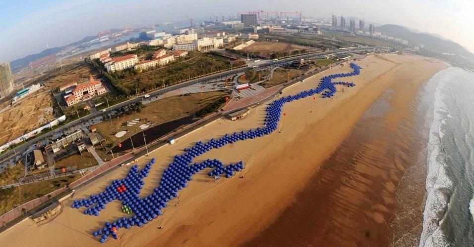 14.nov.2012 - Cerca de 900 tendas formam um gigante dragão chinês, nas areias da praia de Qingdao, na província de Shandong (China). O feito foi reconhecido pelo Livro dos Recordes como o maior quebra-cabeças de tendas do mundo