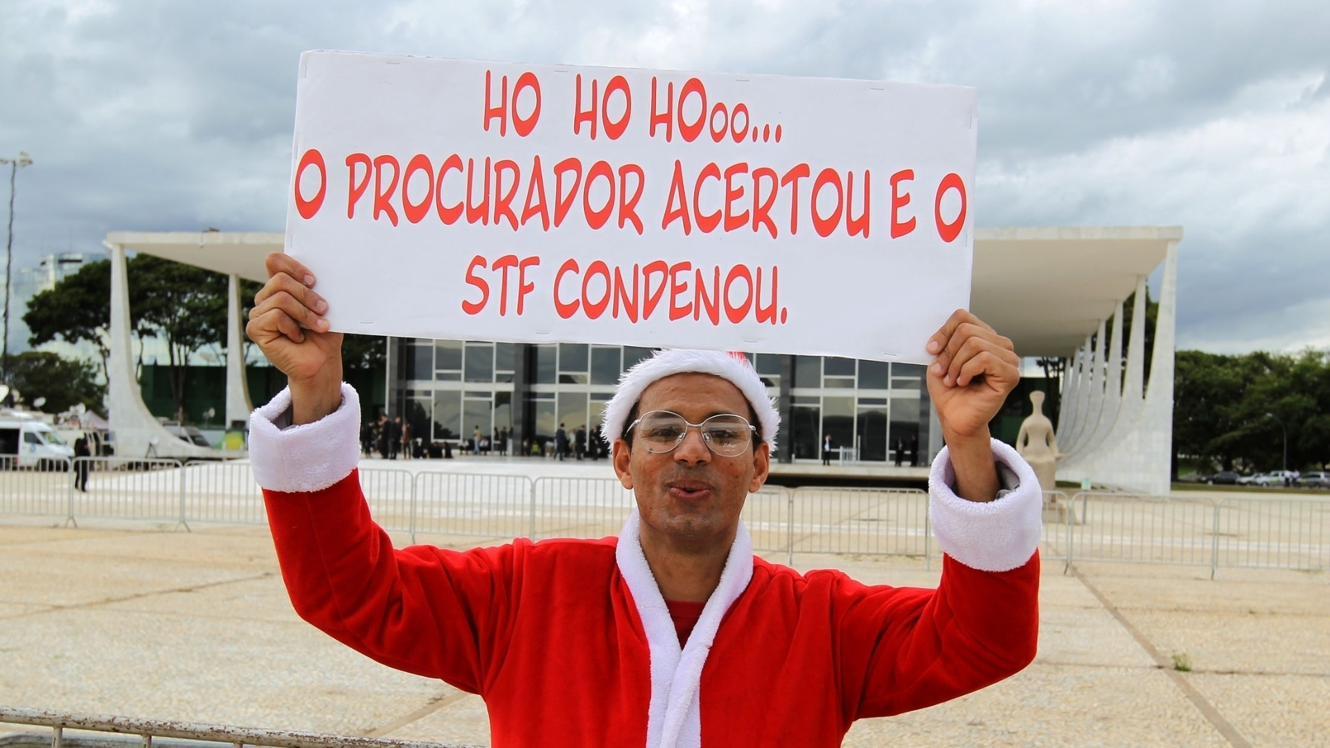 14.nov.2012 - Manifestante vestido de Papai Noel carrega placa do lado de fora do Supremo Tribunal Federal, durante julgamento do mensalão.