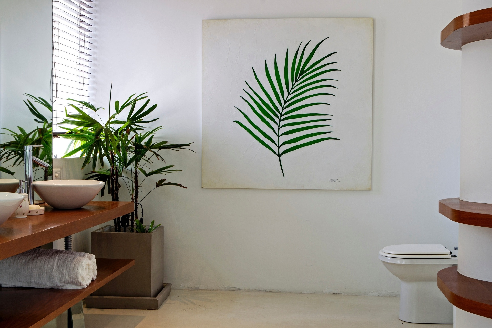 O banheiro da suíte máster acompanha o estilo do apartamento Copacabana, reformado pelo escritório House In Rio: cimento queimado no piso, bancada de madeira peroba e quadro de Ana Amélia Metzavah