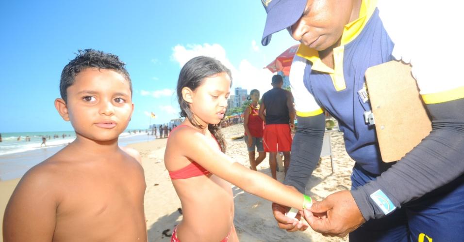 15.nov.2012 - Agente do projeto Criança Segura/Anjos da Guarda coloca pulseiras em crianças para facilitar a identificação e monitoramento dos frequentadores da praia em Jaboatão dos Guararapes (PE), nesta quinta-feira (15)