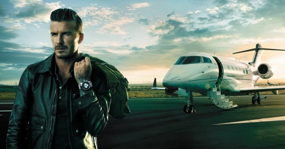 De jaqueta de couro, cara de mau e com um avião ao fundo, David Beckham posa para a nova campanha da marca de relógios Breitling (novembro/2012)