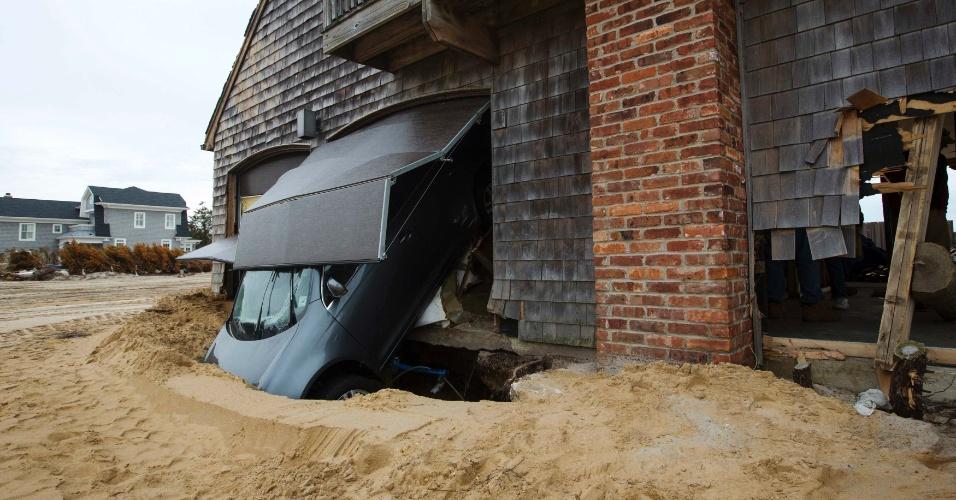16.nov.2012 - Carro que foi jogado para fora da garagem de uma casa na cidade de Mantoloking, em Nova Jersey, durante a passagem da tempestade Sandy permanece atravessado no muro da residência