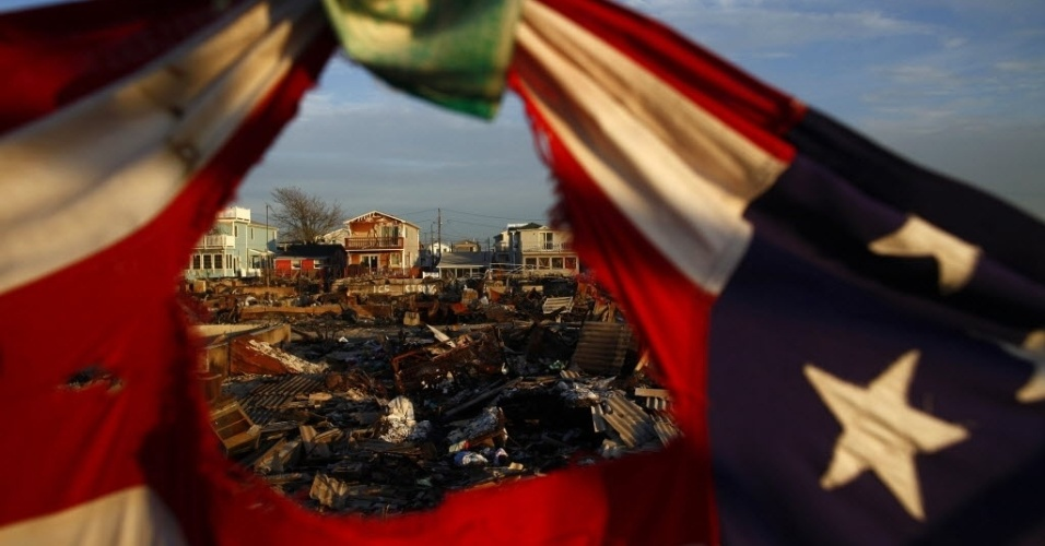 16.nov.2012 - Casas e bandeira dos Estados Unidos destruídas no bairro Breezy Point, em Nova York, durante o furacão Sandy