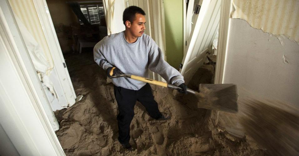 16.nov.2012 - Homem remove areia de dentro de casa danificada pela passagem da tempestade Sandy, em Mantoloking, Nova Jersey (EUA)