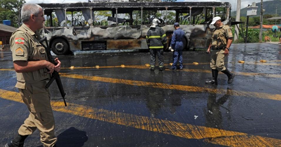 16.nov.2012 - Policiais observam ônibus queimado em São José, na Grande Florianópolis. De acordo com testemunhas, criminosos mandaram os passageiros saírem e incendiaram o veículo. O ataque aconteceu na SC-407