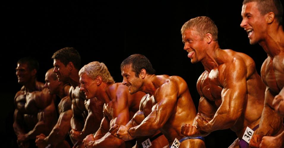 Homens que participam do Strongo Cup, torneio de fisiculturismo na Rússia, fazem força e exibem os músculos