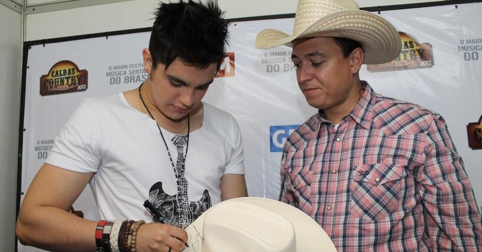 Luan Santana autografa chapéu do animador Cuiabano Lima nos bastidores do Caldas Country Show (16/11/2012)
