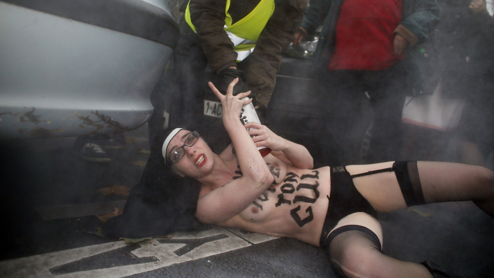 18.nov.2012 - Ativista do grupo feminista Femen  contida durante protesto neste domingo, em Paris (Frana), contra a oposio da Igreja Catlica ao casamento gay