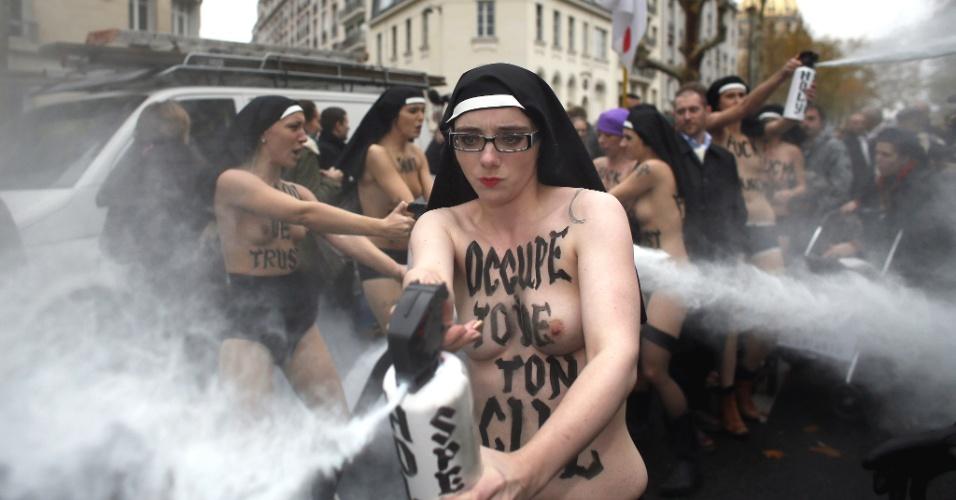 18.nov.2012 - Ativistas do grupo feminista Femen usam spray durante protesto, em Paris (França), contra a oposição da Igreja Católica ao casamento gay