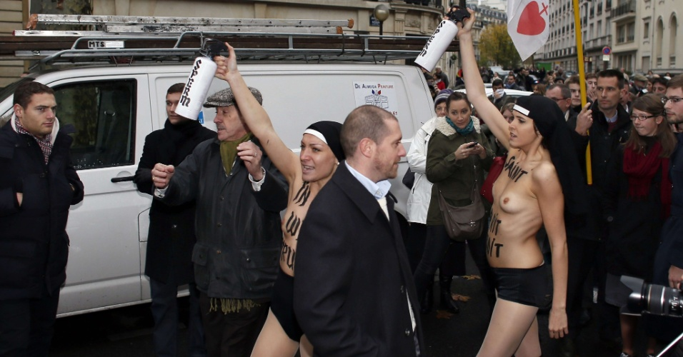 18.nov.2012 - Militantes francesas e ucranianas do movimento feminista Femen exibiram os seios nas ruas de um bairro popular de Paris em protesto à oposição da Igreja Católica ao casamento gay
