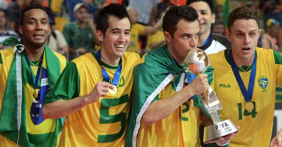 Ao lado dos companheiros de seleção, Falcão carrega e beija a taça da Copa do Mundo de futsal