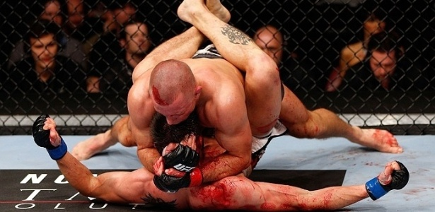 Georges St-Pierre e Carlos Condit lutam no cho durante combate pelo cinturo dos meio-mdios no UFC 154
