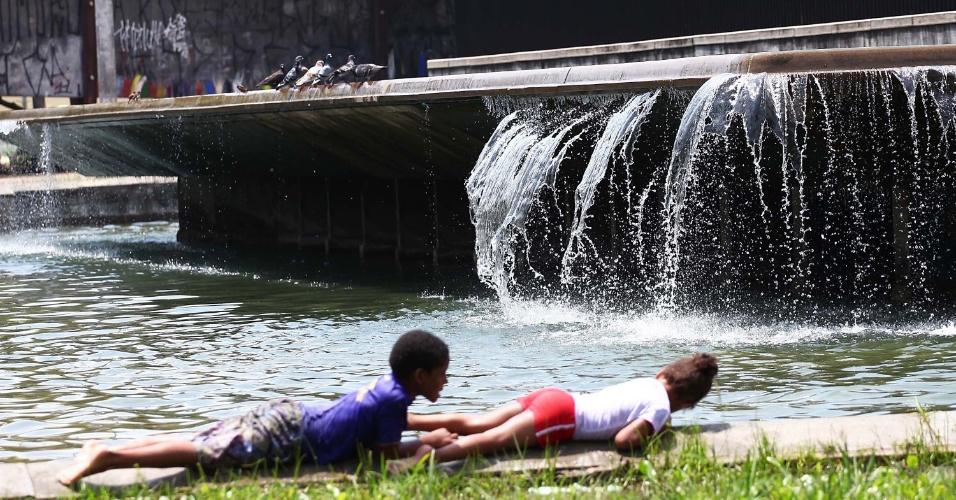 19.nov.2012 - Crianças brincam perto de fonte no centro de São Paulo no começo da tarde desta segunda-feira (19)
