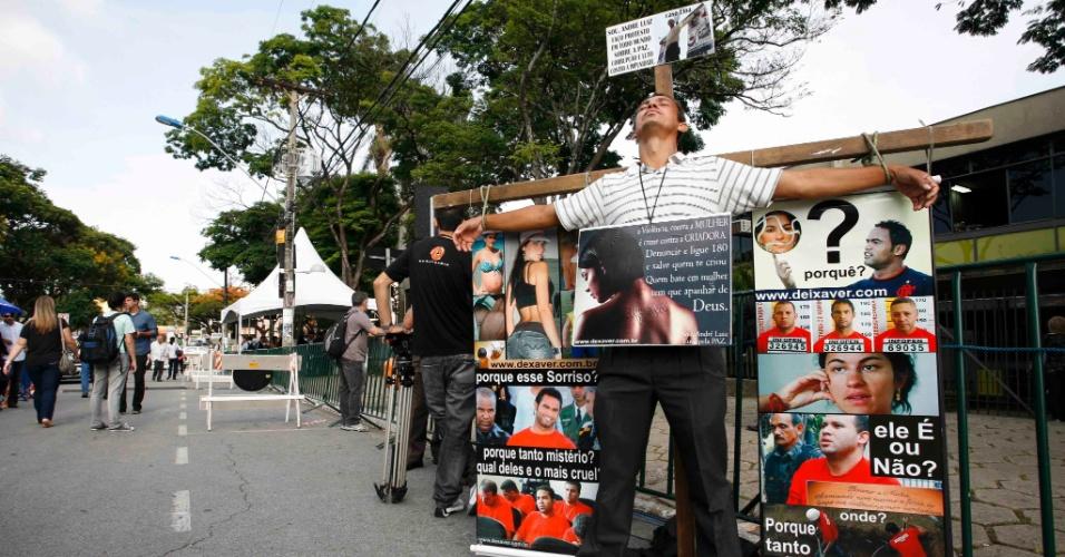 19.nov.2012 - Homem se acorrenta em uma cruz com fotos de Eliza Samudio e do goleiro Bruno na porta do Fórum Doutor Pedro Aleixo, em Contagem (MG)