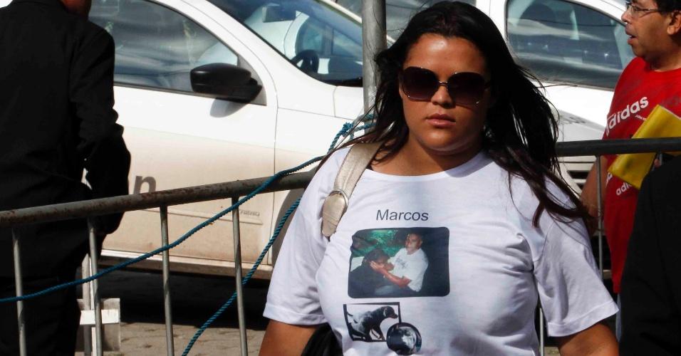 19.nov.2012 - Midian Kelly, filha de Marcos Aparecido dos Santos, o Bola, chega ao Fórum Doutor Pedro Aleixo, em Contagem (MG), vestindo uma camiseta com a foto do pai ao lado dos seus cães. O primo do goleiro Bruno, também suspeito de participação no desaparecimento da ex-modelo, disse à polícia que Eliza tinha sido esquartejada e que viu os cachorros de Bola comerem a mão dela. Depois, negou a versão. Os cachorros morreram em 2010