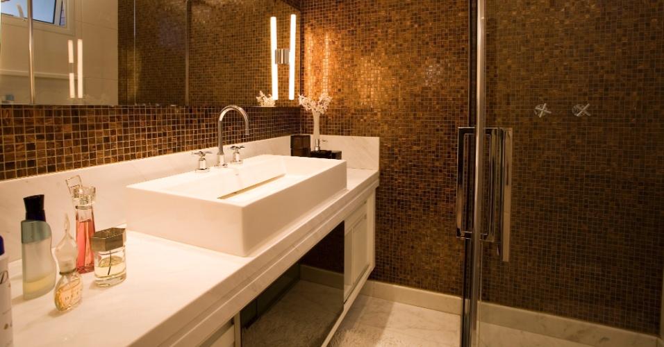 Apesar de possuir apenas 4 m², este banheiro planejado por Shenia Nogueira parece bem maior. O segredo está na bancada de mármore que apoia a ampla cuba e nas paredes azulejadas preexistentes (opostas ao lavatório) que foram mantidas. Para quebrar com o branco predominante, Nogueira aplicou pastilhas acobreadas da Bizzasa e, no box, o chuveiro com cromoterapia proporciona relaxamento e conforto