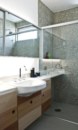 Um dos banheiro da casa reformada pelo escritório Arqdonini, com 4,37 m², ganhou gabinete com estrutura de compensado, revestida por laminado texturizado em diferentes padrões, da Formica. No ambiente, a parede do box é forrada por porcelanato estampado Navarti que imita pedras roladas. Driblando a área diminuta, o projeto beneficiou-se pela bancada que avança a área do chuveiro e serve como aparador para produtos de banho