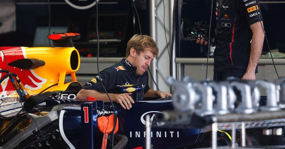 23.nov.2012 - Ainda sem o macacão, Sebastian Vettel entra em sua Red Bull antes dos treinos livres desta sexta-feira em Interlagos