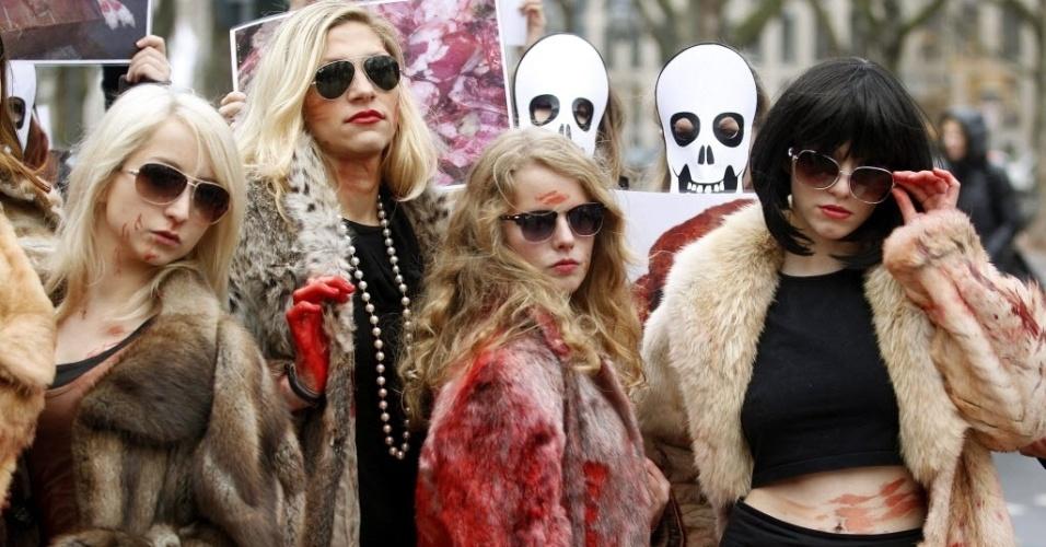 23.nov.2012 - Ativistas do grupo Peta, que defende o direito dos animais, protestam vestidas com casacos de pele manchados de sangue, nesta sexta-feira (23) em Düsseldorf, na Alemanha