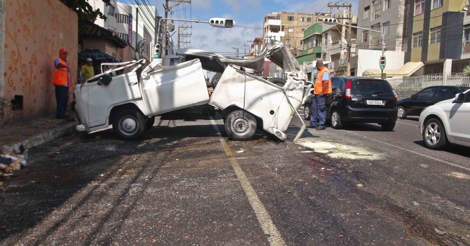 23.nov.2012 - Funcionários da prefeitura observam os destroços de uma kombi que capotou nesta sexta-feira (23) em Salvador. O veículo transportava pães, e ao menos duas pessoas feridas