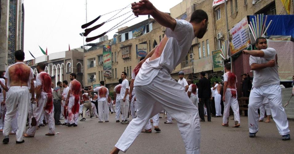 23.nov.2012 - Muçulmanos xiitas realizam o ritual de autoflagelação com facas e correntes, durante uma procissão religiosa em Kerbala, próximo de Bagdá, no Iraque. Milhares de xiitas iraquianos vão visitar a cidade sagrada de Kerbala na semana que marca a morte de Hussein, neto do profeta Maomé