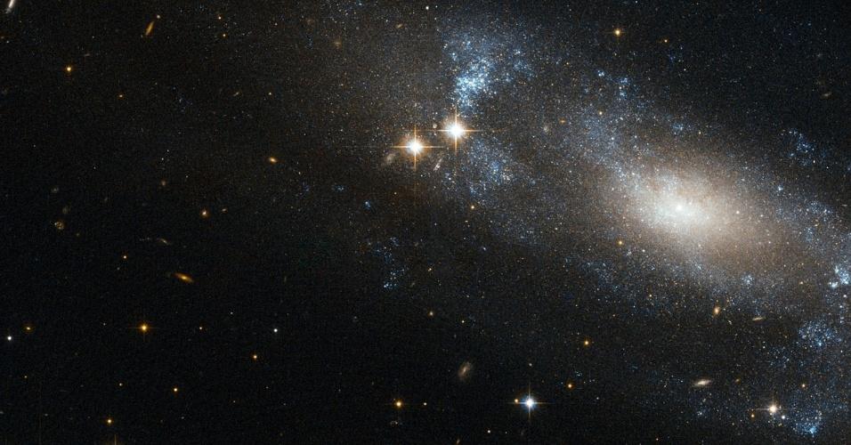23.nov.2012 - O telescópio Hubble detectou a galáxia espiral ESO 499-G37 e fez novas imagens do objeto diante de uma região do céu bastante estrelado, revelando suas principais características. Seus braços espirais, que contém poeira e gás quente, parecem ser azuis por concentrar suas estrelas mais quentes e mais jovens - as mais velhas e frias são empurradas para o núcleo