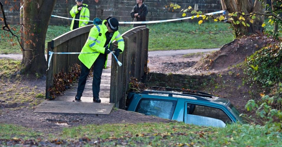 23.nov.2012 - Policiais ingleses observam veículo que ficou preso sob ponte após ser arrastado por uma enchente, nesta sexta-feira (23) em Somerset. O motorista morreu