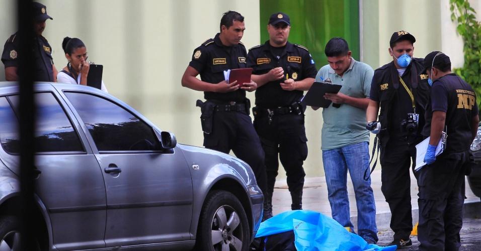 23.nov.2012 - Policiais inspecionam corpo de uma das sete vítimas de um tiroteio em clínica privada na Cidade da Guatemala