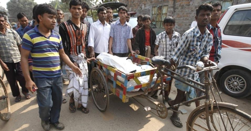 25.nov.2012 - Amigos de vítima de incêndio usam triciclo para transportar o corpo, em Savar, na periferia de Dacca, capital de Bangladesh
