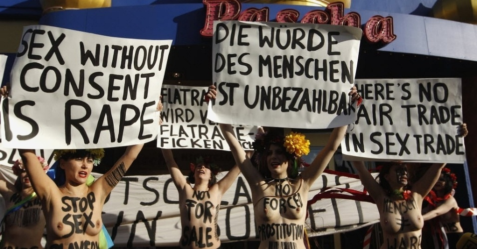 25.nov.2012 - Ativistas feministas do grupo Femen protestam em frente ao bordel Pascha, o maior da Europa, na cidade alemã de Colônia. Nos cartazes, se lê, em inglês,
