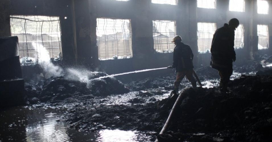 25.nov.2012 - Bombeiros continuam a controlar últimos focos de incêndio no que restou da fábrica Tazren, em região próxima a Dacca, capital de Bangladesh