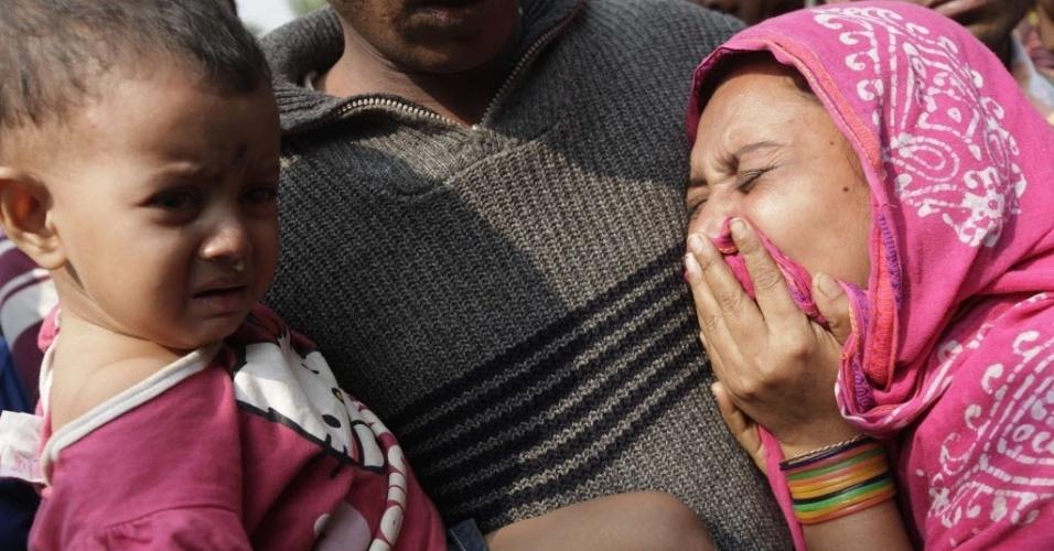 25.nov.2012 - Familiares choram a morte de vítima de incêndio em fábrica têxtil na periferia de Dacca, em Bangladesh. O fogo começou na noite de sábado (24), e matou ao menos 121 pessoas