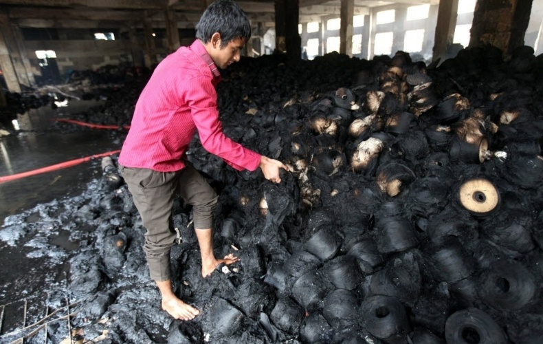 25.nov.2012 - Homem recolhe algodão queimado após incêndio em fábrica têxtil na periferia de Dacca, capital de Bangladesh