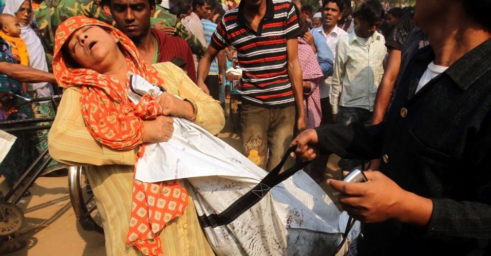 25.nov.2012 - Mulher desmaia ao receber corpo de parente vítima de incêndio que consumiu uma fábrica têxtil