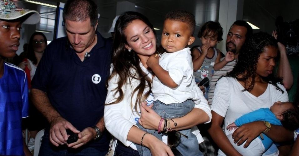 Bruna Marquezine brinca com bebê durante o evento Ação Global, no Complexo do Alemão, no Rio de Janeiro (25/11/12)