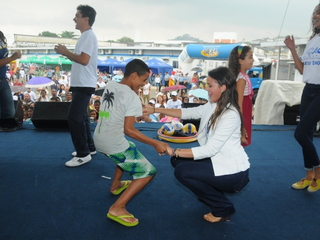 Bruna Marquezine dança com menino no evento Ação Global, no Complexo do Alemão, no Rio de Janeiro (25/11/12)