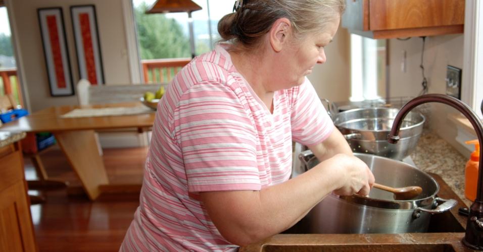 mulher lavando a louça, mulher lava louça na pia, mulher, meia idade, lavando louça