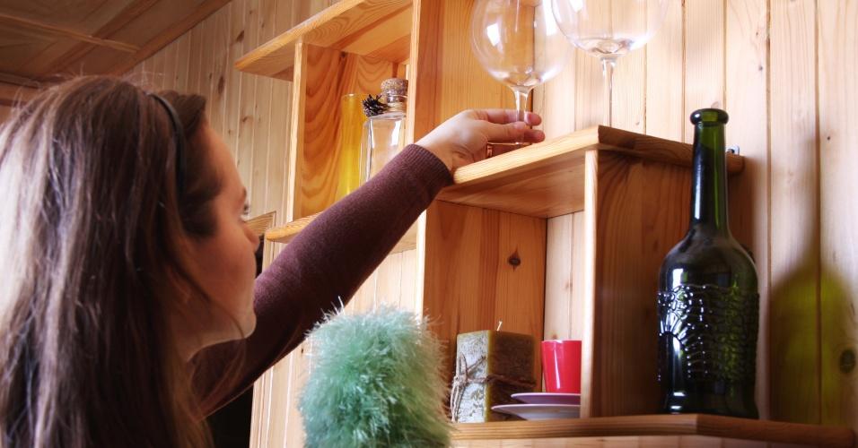 mulher tirando o pó de taças, mulher tirando o pó de itens que estão no alto, ilustra