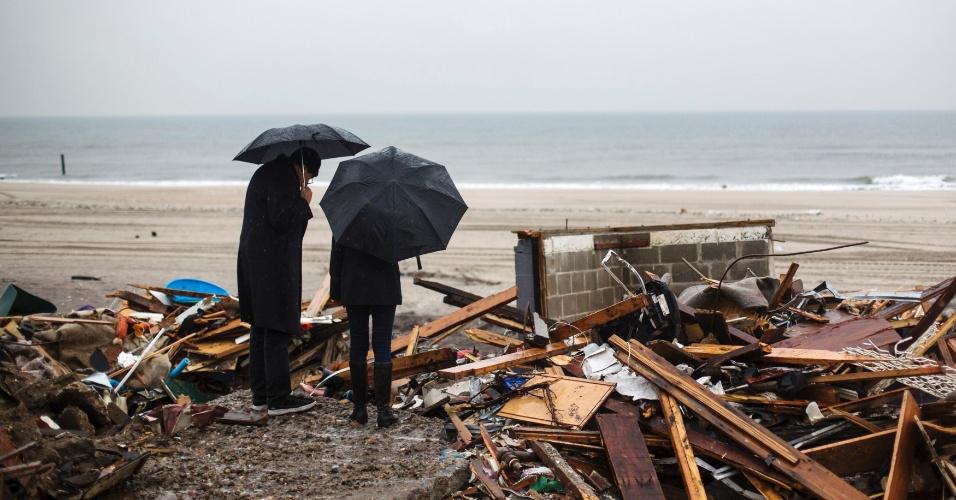 27.nov.2012 - Os donos de uma casa em Nova York visitam os escombros de seu imóvel, destruído pela passagem do furacão Sandy