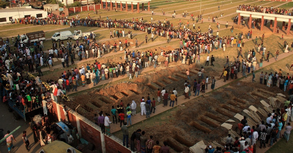 27.nov.2012 - Pessoas participam do enterro da algumas das 110 vítimas do incêndio em uma manufatura, nesta terça-feira (27) em Dacca (Bangladesh). Manifestantes protestaram contra as condições de trabalho nas fábricas pelo segundo dia consecutivo