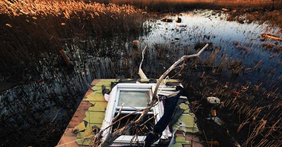 28.nov.2012 - Pedaço de uma casa destruída pelo furacão Sandy repousa numa área alagada na região de Staten Island, em Nova York