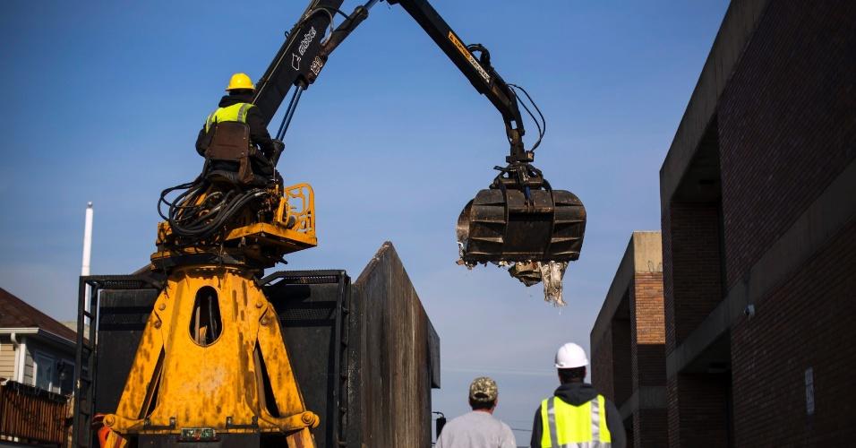 29.nov.2012 - Homens usam guindaste para retirar detritos que ainda ficaram nas ruas de Nova York, mesmo após um mês da passagem do furacão Sandy nos Estados Unidos