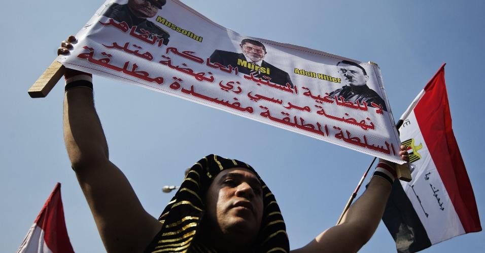30.nov.2012 - Egípcio segura faixa em que o atual presidente do país, Mohamed Mursi (centro), aparece ao lados dos ditadores Benito Mussolini (Itália) e Adolf Hitler (Alemanha). Os manifestantes se reúnem na praça Tahrir para protestar contra o governo de Mursi, no Cairo