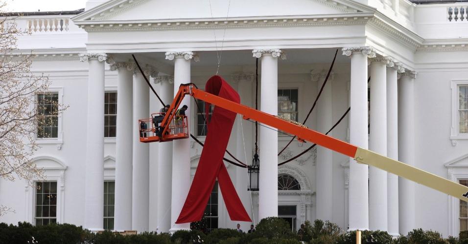 30.nov.2012 - Operários fixam um grande laço vermelho, símbolo da luta contra a Aids, no pórtico da Casa Branca, em Washington. Neste sábado (1) será celebrado o Dia Mundial de Luta contra a Aids